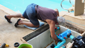 a man finding a leak in an inground pool pipe